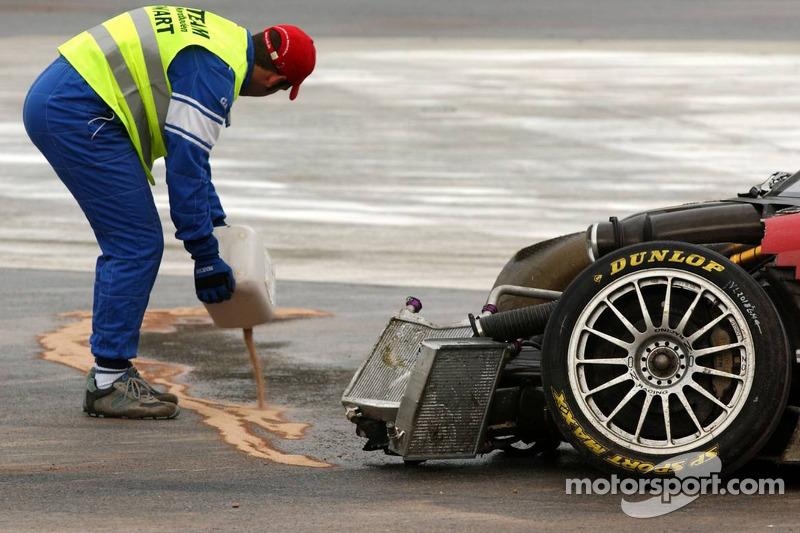Un commissaire nettoie le liquide dégagé par la voiture de Vanina Ickx