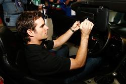 Jeff Gordon effectue un autographe sur la vitre de sa Corvette de 2005, qui a été mise en jeu lors d'un tiragepour la Fondation Jeff Gordon