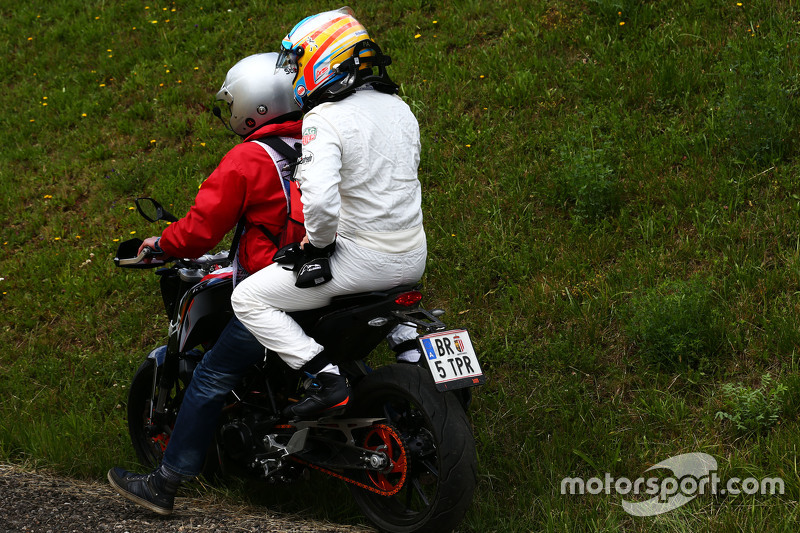 Race retiree Fernando Alonso, McLaren returns to the pits on a motorbike