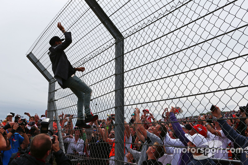 Lewis Hamilton, Mercedes AMG F1 climbs hte fence to greet the fans