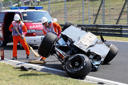 Oficiales de seguridad atienden al accidentado Sahara Force India de Sergio Pérez.