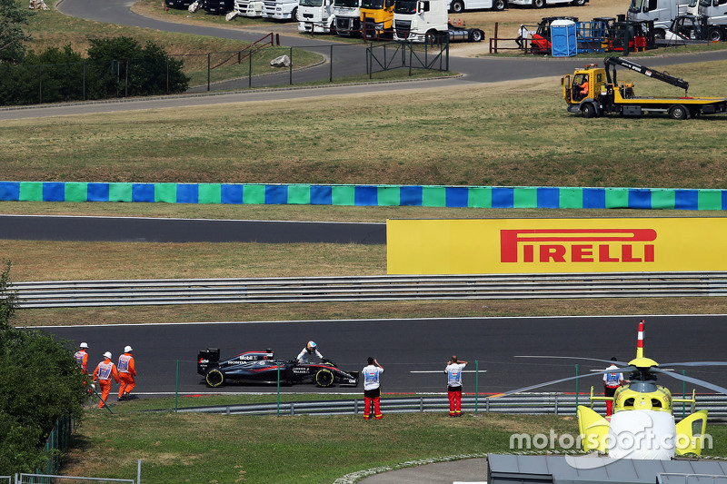 Fernando Alonso, pushes his McLaren MP4-30 into the pit lane during qualifying