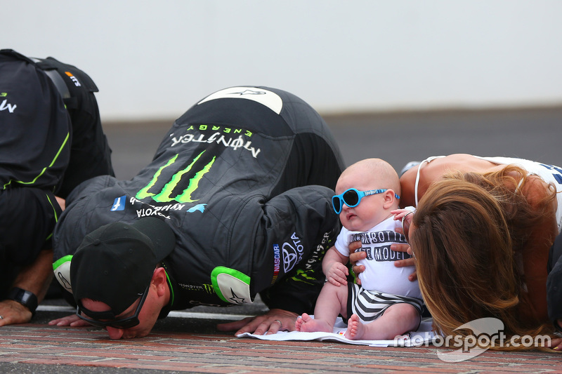 Race winner Kyle Busch kisses the bricks with his family