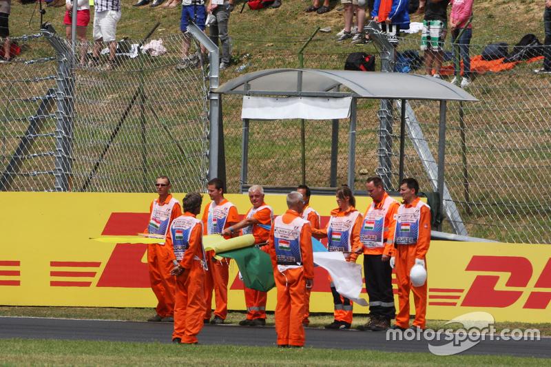 Marshals observe the pre-race tribute to Жуль Бьянкі