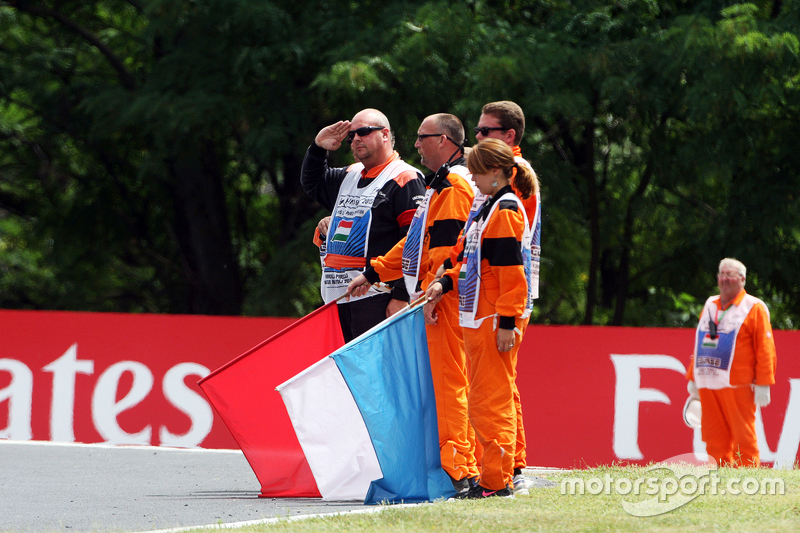 Marshals observe the pre-race tribute to Жуль Бьянкі