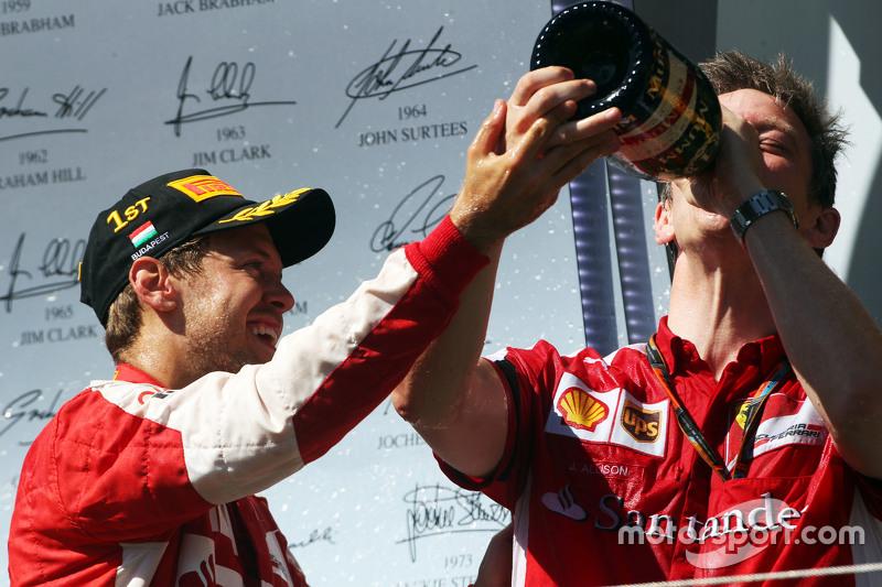 Juara balapan Sebastian Vettel, Ferrari merayakan di podium bersama James Allison, Ferrari Chassis T