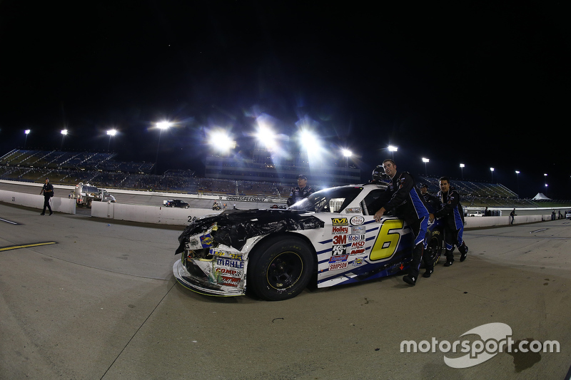 Roush Fenway Racing mechanics push the damaged Ford of Darrell Wallace Jr.