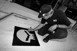 Corvette Racing team member signs the C6.R logo on the pitlane