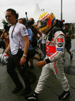 Lewis Hamilton, McLaren Mercedes, returns to the paddock after retiring from the race