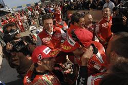 Race winner Casey Stoner celebrates with Loris Capirossi