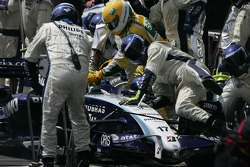 A Williams mechanic is knocked to to floor by Kazuki Nakajima Williams F1 Team during a pit stop