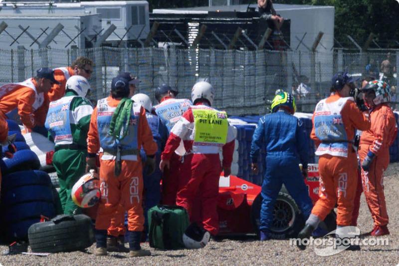 Miembros del equipo de seguridad asisten el auto tras el accidente de Michael Schumacher