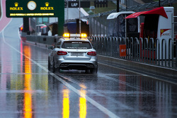 The FIA Medical Car drives through a wet and rainy pit lane