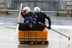 Sauber F1 Team mechanics practice their boating skills in the wet pit lane