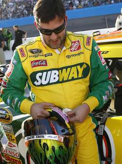 Tony Stewart applies a decal in a tribute to fallen Sprint Cup official Brienne Davis on his helmet