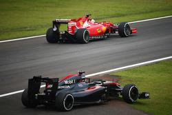 El McLaren MP4-30 de Fernando Alonso, McLaren pasa por Sebastian Vettel, Ferrari en la segunda sesi