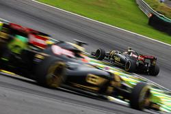 Пастор Мальдонадо, Lotus F1 E23 едет впереди Роменга Грожана, Lotus F1 E23