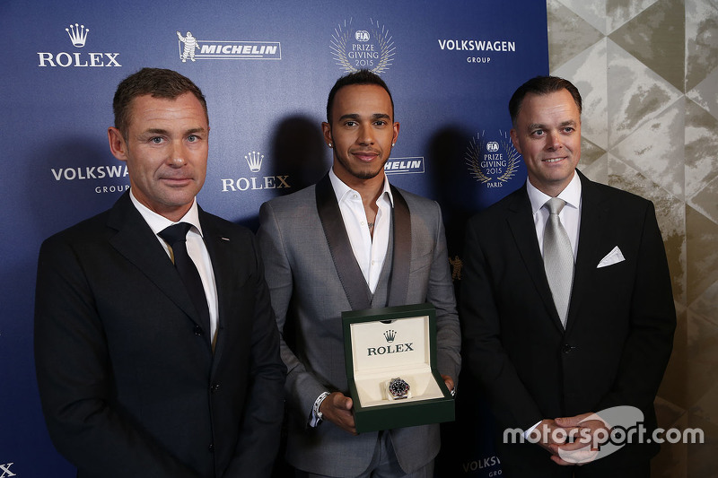 Lewis Hamilton gets a Rolex watch, flanked by Tom Kristensen.
