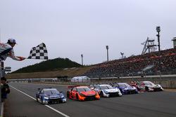 Takuma Sato waves the checkered flag over the Super GT Honda entries