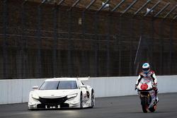 Fernando Alonso rides a Honda bike with the Honda NSX