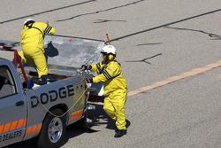 L'équipe de sécurité répand de quoi laisser la piste sèche durant la séance d'essais