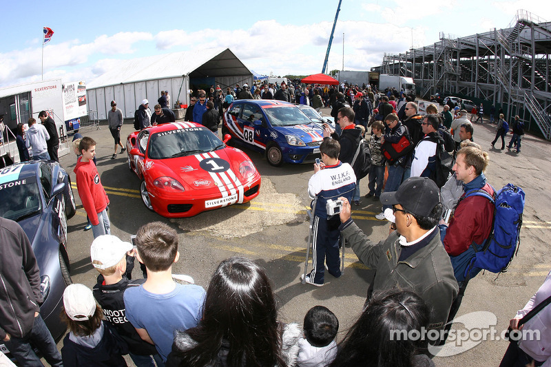 Fans take pictures of cars in the paddock