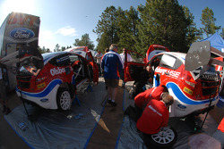 The Ford Fiestas are worked on prior to the start of the race