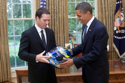 Three-time defending NASCAR Sprint Cup Series champion Jimmie Johnson presents President Barack Obama with a helmet in the Oval Office at the White House in Washington, D.C.