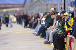 Crew members and fans sit along pit wall during qualifying
