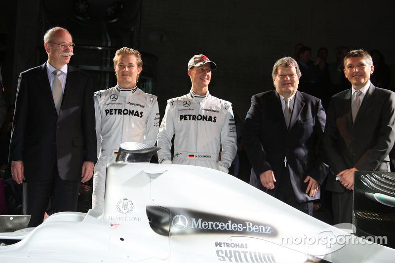 Dr. Dieter Zetsche, Nico Rosberg, Michael Schumacher, Norbert Haug et  Nick Fry posent avec la Brawn GP de 2009 décorée de la nouvelle livrée 2010