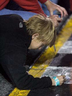 Fans sign the start-finish line