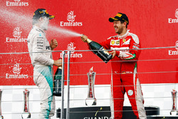 (L to R): Race winner Nico Rosberg, Mercedes AMG F1 celebrates with the champagne on the podium with second placed Sebastian Vettel, Ferrari